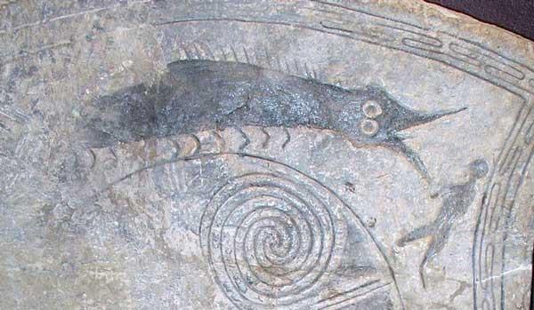 Fotografi av detalj på bildsten, föreställande en person framför ett odjur.
