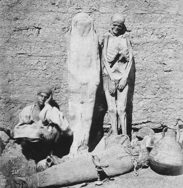 Vilande handelsman bredvid flera mumier.