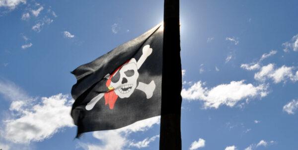 Bild på en piratflagga mot en blå himmel