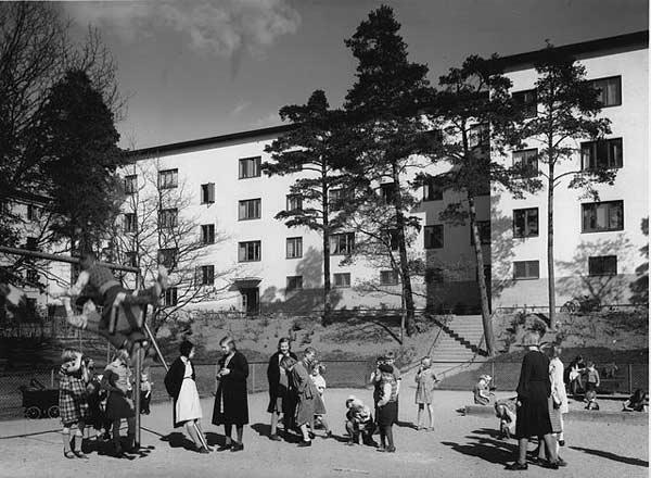 Svartvitt fotografi föreställande barn och tonåringar på lekplats framför ett flerfamiljshus
