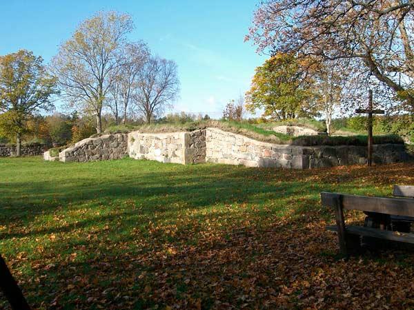 Ruin med murar i sten samt ett träkors