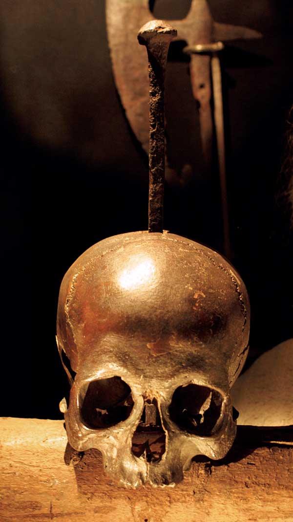 Bild som visar en skalle spetsad med en rostig järnspik
